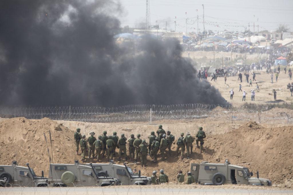 """Tirs de gaz lacrymogène et à balles réelles de l'armée israélienne durant une manifestation sur la """"ligne verte"""". Les palestinien·nes tentent d'échapper à la vue des soldat·es israélien·nes en brûlant des pneus. La photo est prise depuis le kibbutz de Nahal Oz, dans le sud d'Israël • 13 avril 2018 • Oren Ziv / Activestills.org"""